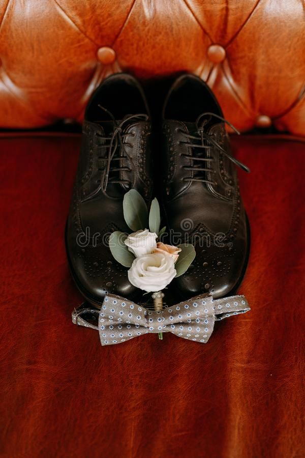 Men`s black wedding shoes are located on the leather sofa royalty free stock photo