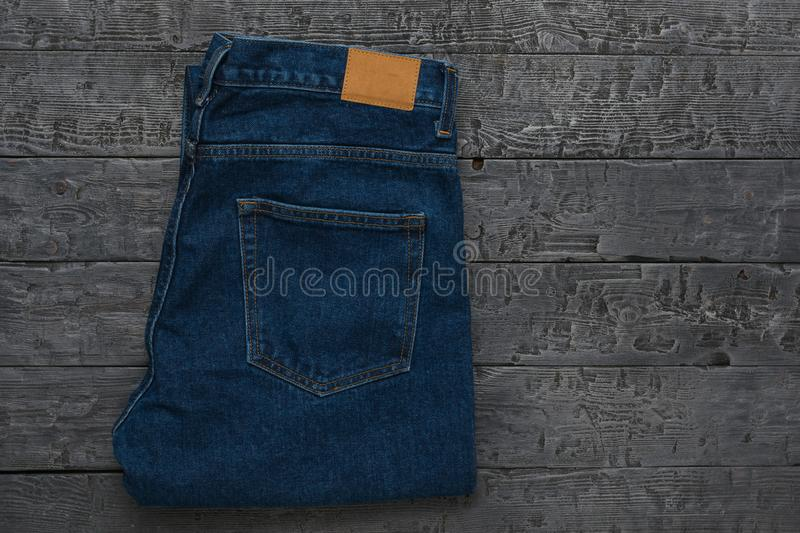 Men`s blue jeans on a dark wooden table. Classic denim clothing. Flat lay. The view from the top stock photo
