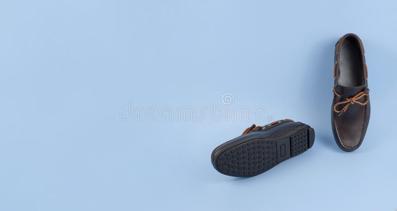 Men`s brown suede moccasins, loafers isolated blue background royalty free stock image