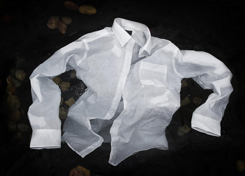 Men's button up shirt floating or sinking in water royalty free stock photos