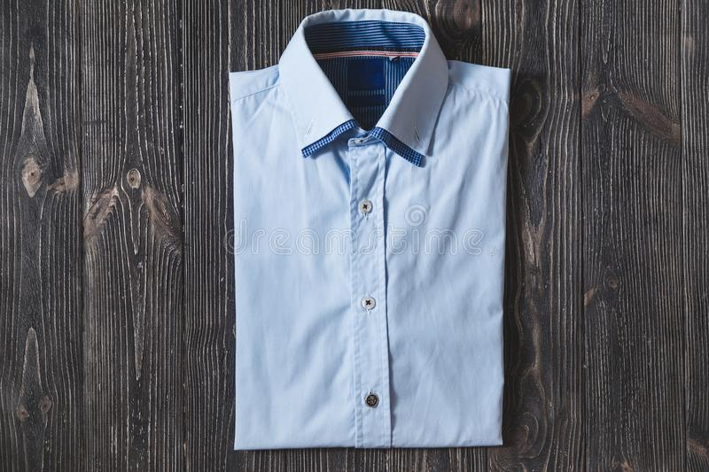Men`s classic blue folded cotton shirt with long or short sleeve on black brutal background. royalty free stock photography