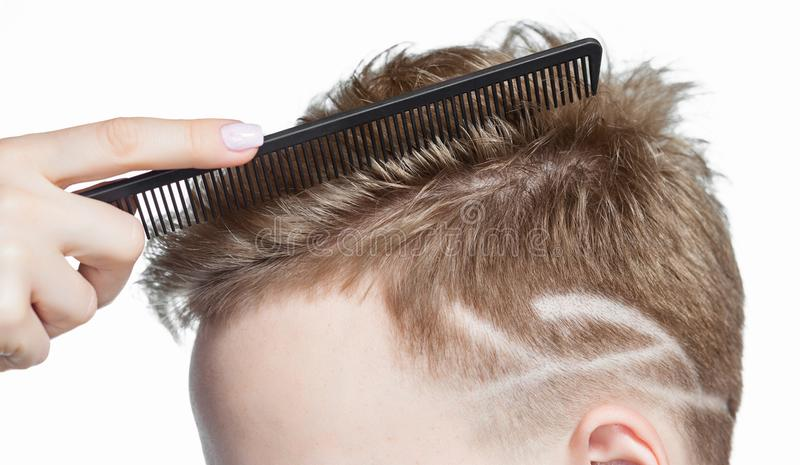 Men`s creative haircut in the beauty salon. Hair care and hair styling.  stock image