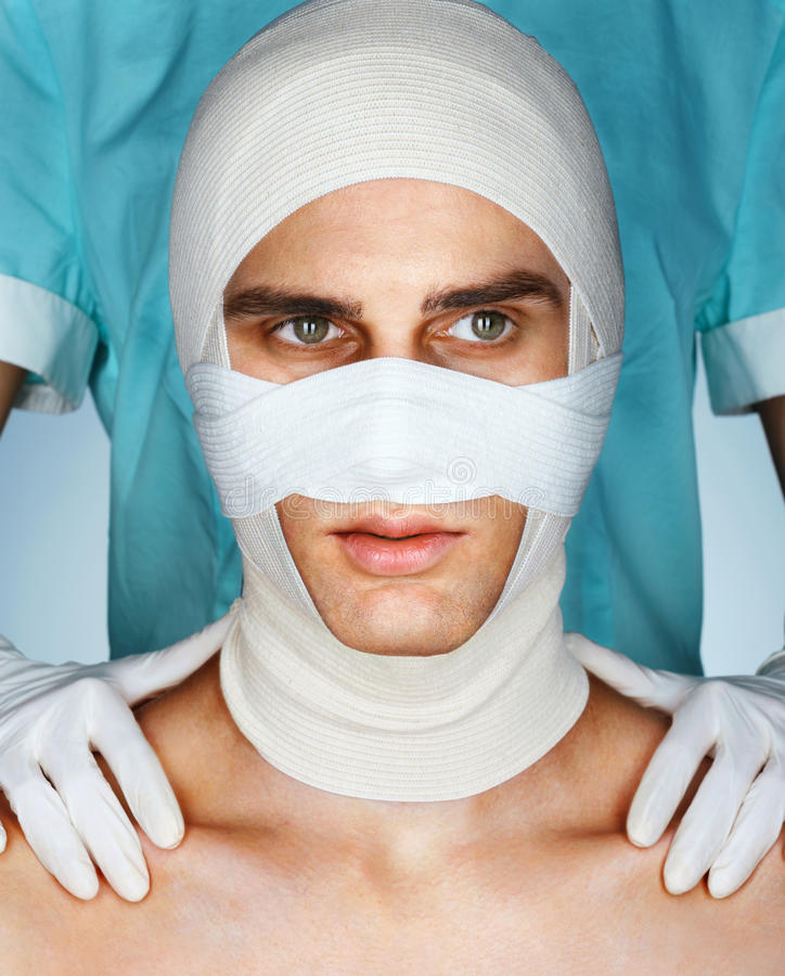 Men's face in medical bandage after beauty Plastic Surgery stock image