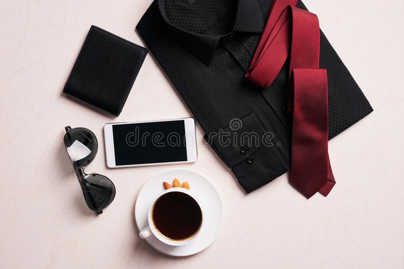 Men`s fashion clothing with several accessories. Glasses, mobile phone, black leather walet and cup of hot coffee, on white background, top view stock image