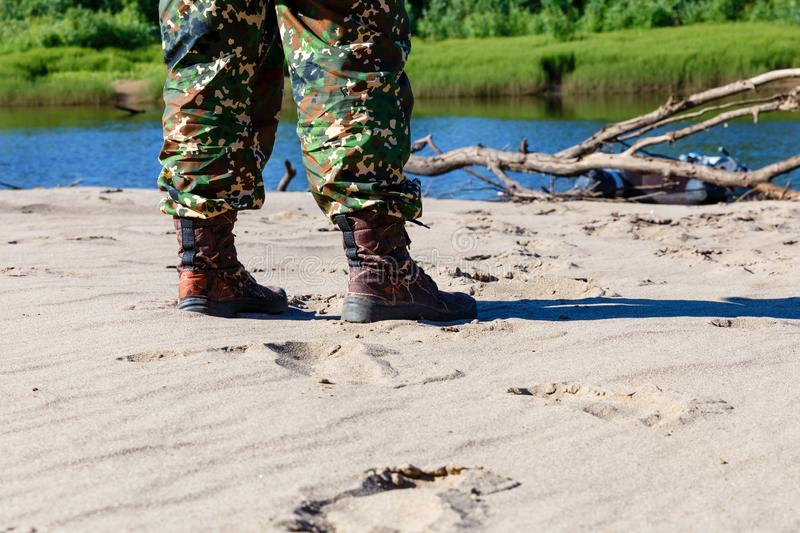 Men`s feet in boots by the river royalty free stock image