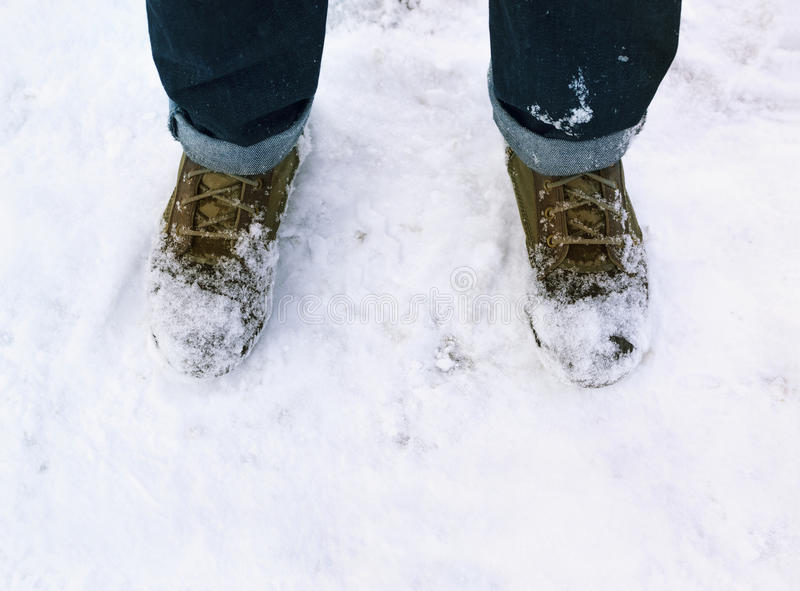 Men`s feet and shoes in snow. Winter season stock photos