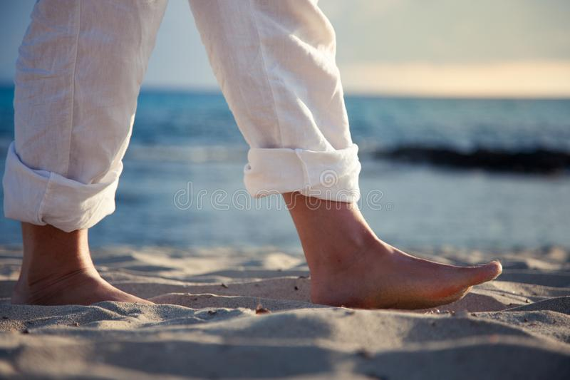 Men`s feet walk barefoot on the beach sand at dawn stock images