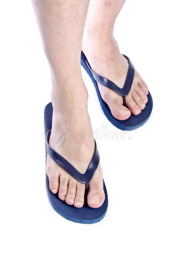 Men's Feet Wearing Navy Blue Flop Flops #1. Men's Feet Wearing Navy Blue Flop Flops Isolated on White #1 royalty free stock photos