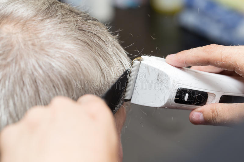 Men`s haircut at the beauty salon machine.  royalty free stock images