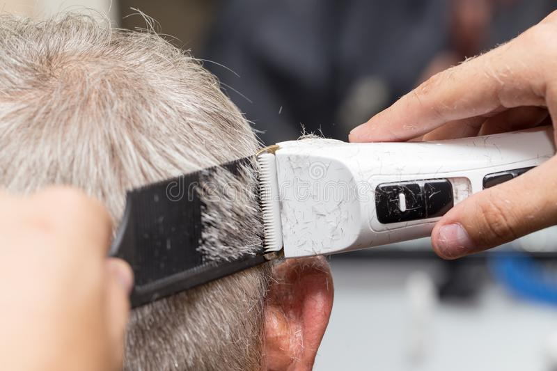Men`s haircut at the beauty salon machine.  royalty free stock photography