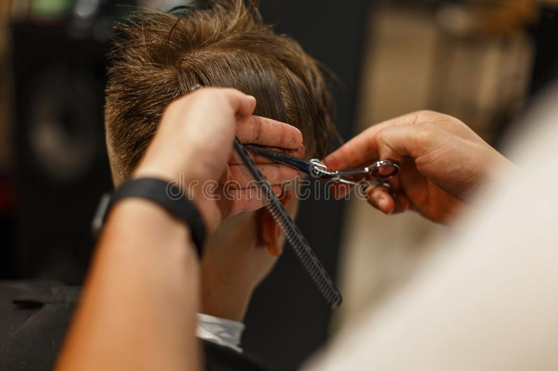 Men`s haircut. Professional hairdresser doing hairstyle royalty free stock image