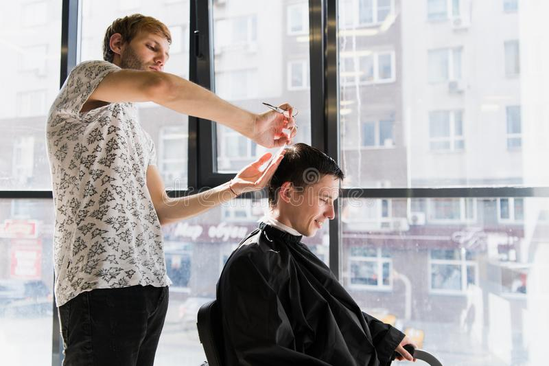 Men`s hairstyling and haircutting in a barber shop or hair salon stock photos