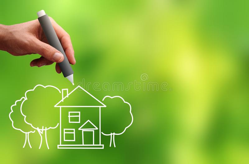 Men's hand draws a house and trees stock photo