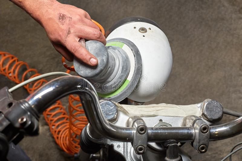 Men`s hand with a grinder polishing motorcycle headlight royalty free stock photos