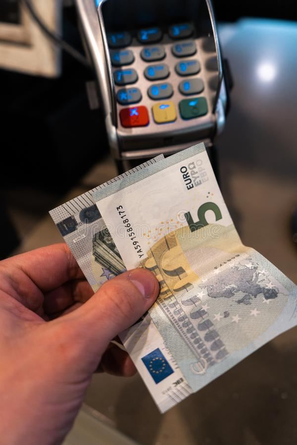 Men`s hand holding EURO banknotes near a payment terminal POS in a cafe stock image