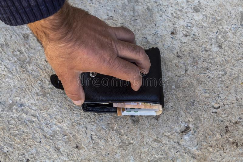 Men`s Hand Trying to Open Black Leather Wallet With Money Inside Which Lays on The Ground royalty free stock photography