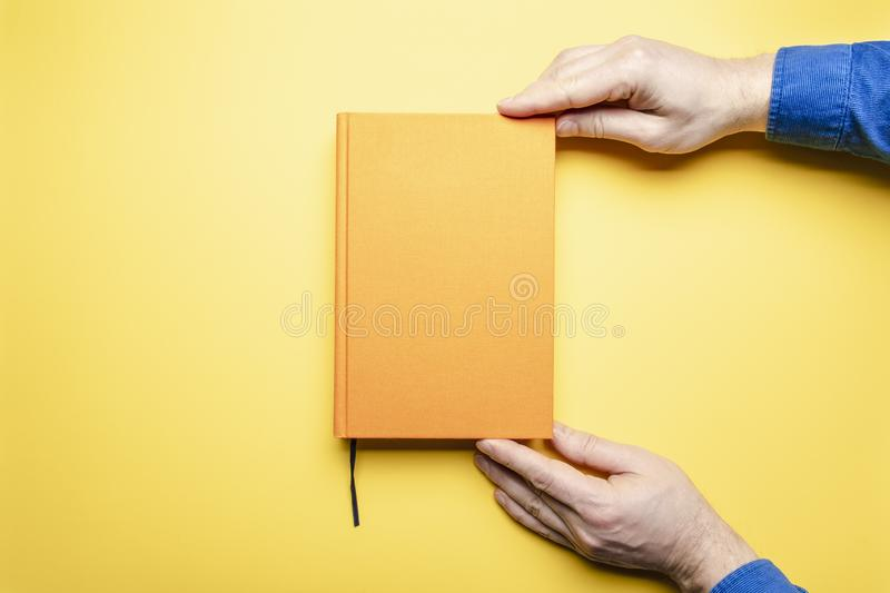 Men`s hands in a blue velvet shirt gently hold the literary work with a bookmark in anticipation of reading, which lies on a. Bright table. The book and the royalty free stock photos