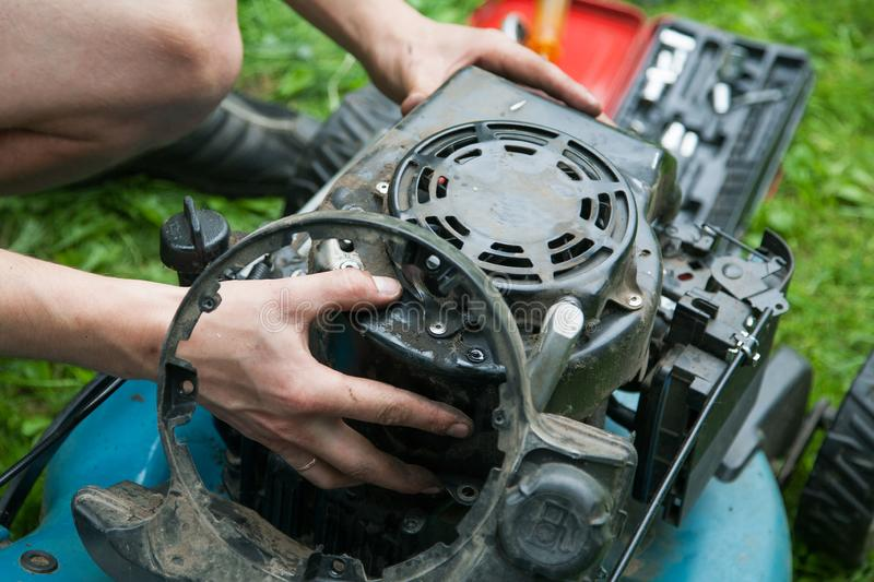 Men`s hands and gasoline engine repair. Close-up stock photography