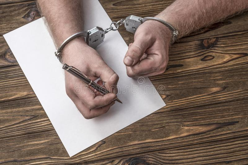 Men`s hands with handcuffs fill the police record, confession. On top see the police investigative detective. Arrest, bail, criminal, prison royalty free stock photo
