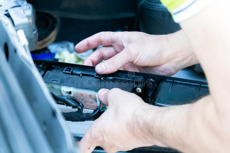 Men`s hands hold a disassembled control panel of power windows, central lock and mirrors in order to find the problem and repair royalty free stock photography
