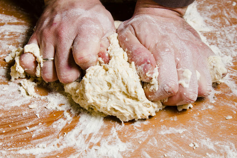 Men's hands knead the dough on the wooden table. The chef prepares the dough for Italian cuisine royalty free stock photos