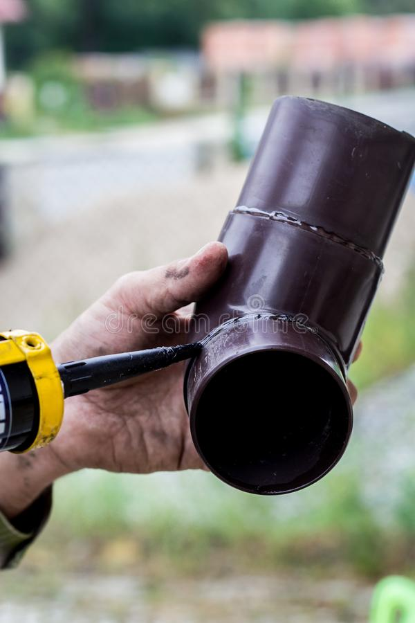 Men`s hands lubricate the gutter with a sealing agent. Housework stock images