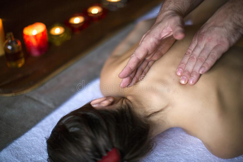 Men`s hands make a therapeutic neck massage for a girl lying on a massage couch. Candles on background. Relax concept. Men`s hands make a therapeutic neck stock image