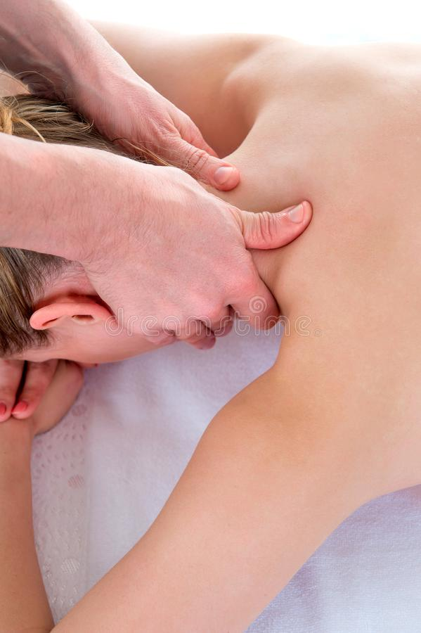 Men`s hands make a therapeutic neck massage for a girl lying on a massage couch in a massage spa royalty free stock image