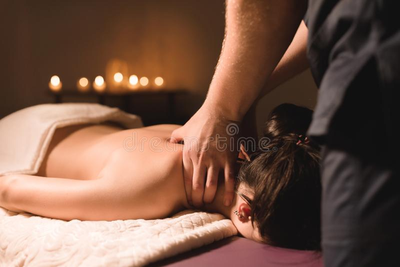 Men`s hands make a therapeutic neck massage for a girl lying on a massage couch in a massage spa with dark lighting. Close-up. Dark Key royalty free stock photo
