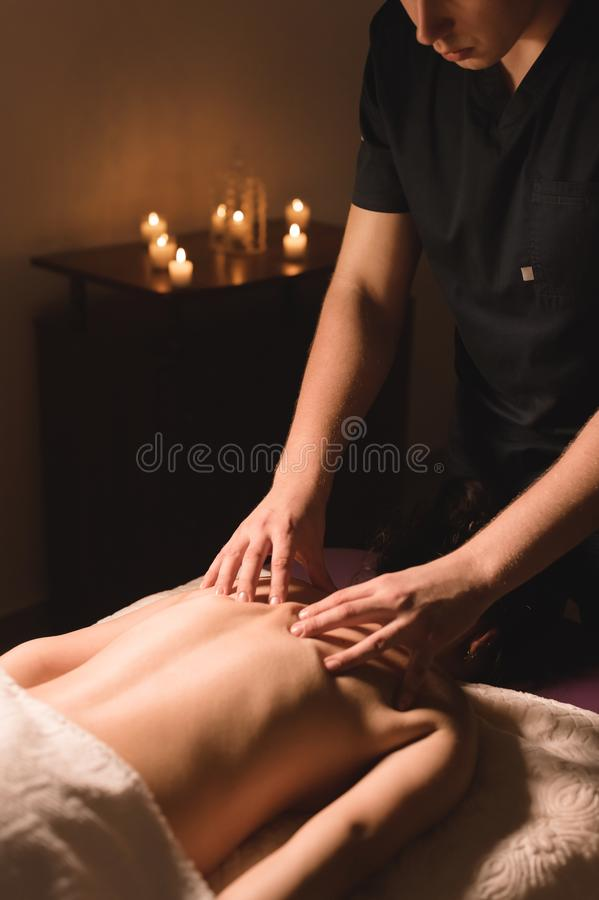 Men`s hands make a therapeutic neck massage for a girl lying on a massage couch in a massage spa with dark lighting. Close-up. Dark Key stock image
