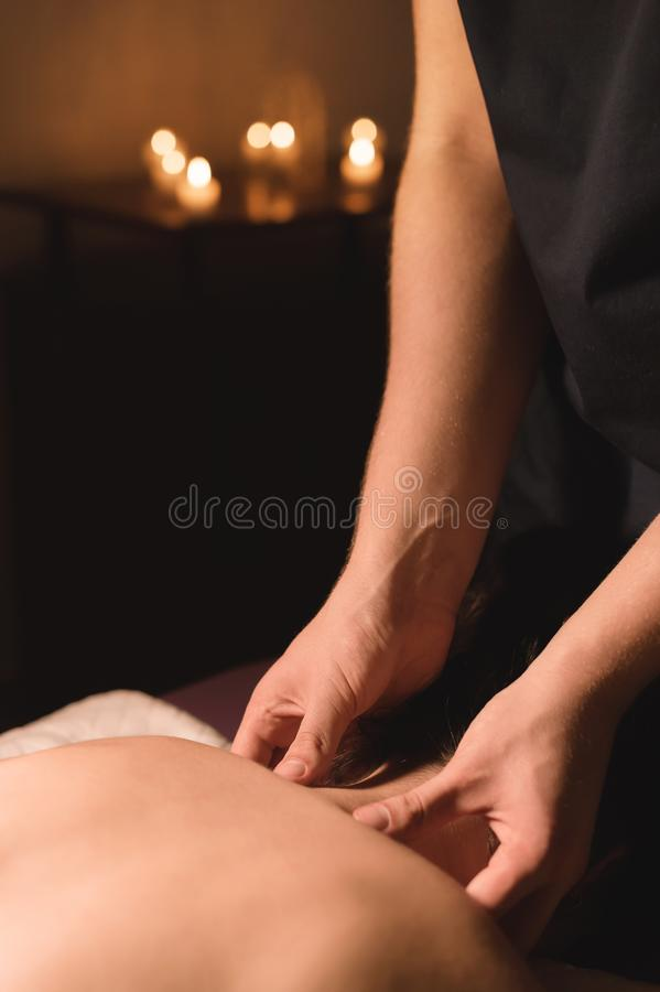 Men`s hands make a therapeutic neck massage for a girl lying on a massage couch in a massage spa with dark lighting. Close-up. Dark Key royalty free stock photography