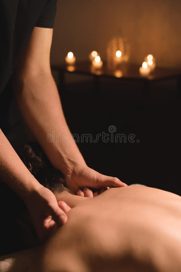 Men`s hands make a therapeutic neck massage for a girl lying on a massage couch in a massage spa with dark lighting. Close-up. Dark Key stock photography