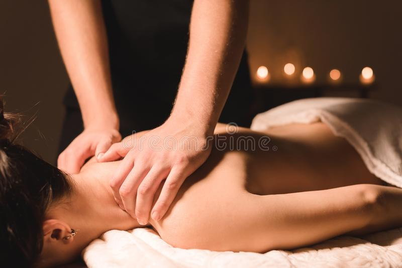Men`s hands make a therapeutic neck massage for a girl lying on a massage couch in a massage spa with dark lighting. Close-up. Dark Key stock images