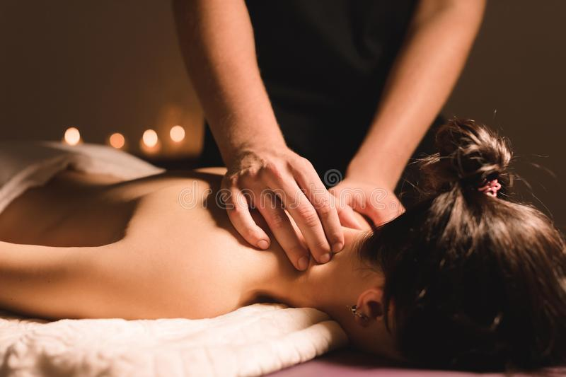 Men`s hands make a therapeutic neck massage for a girl lying on a massage couch in a massage spa with dark lighting. Close-up. Dark Key stock photo