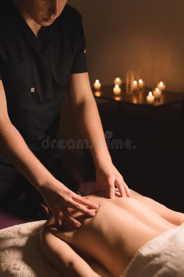 Men`s hands make a therapeutic neck massage for a girl lying on a massage couch in a massage spa with dark lighting. Close-up. Dark Key royalty free stock photos