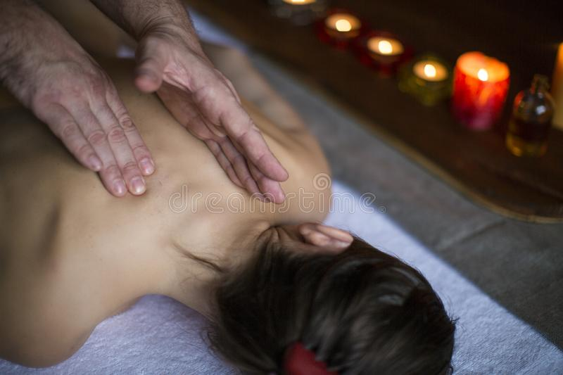 Men`s hands make a therapeutic neck massage for a girl lying on a massage couch in a massage spa with dark lighting. Healthcare, spa and relax concept royalty free stock photography