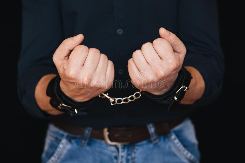 Men`s hands shackled in leather handcuffs close up stock photography