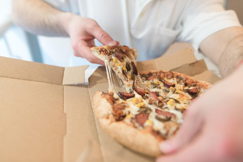Men`s hands take a piece of hot pizza. The man will eat delicious pizza with cheese. Focus on pizza. stock photos