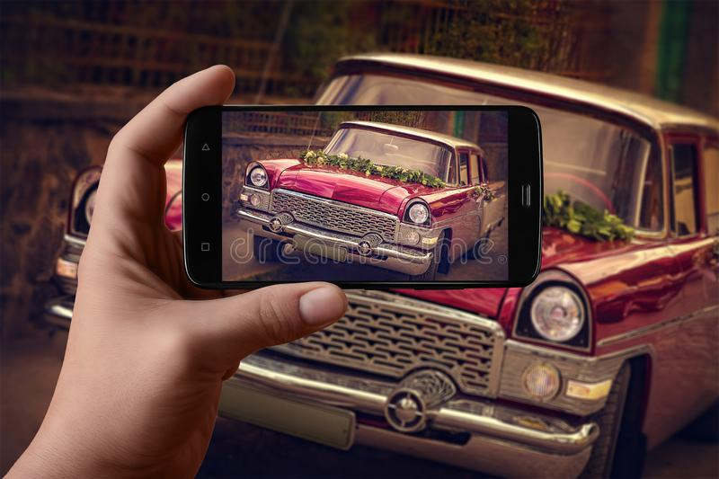 Men`s hands taking pictures of the car on the phone. Vintage festive car royalty free stock photo