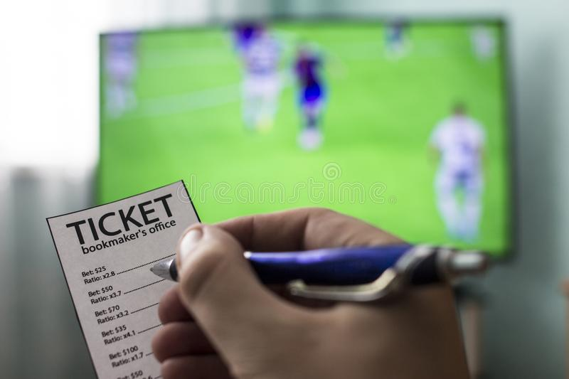 Men`s hands with a ticket bookmaker`s office, on TV show football, Champions League, sports betting, close-ups. World championship stock images