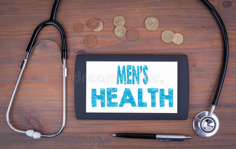 Men`s Health. Device on a wooden table. Men`s Health. Text on tablet device on a wooden table royalty free stock photos