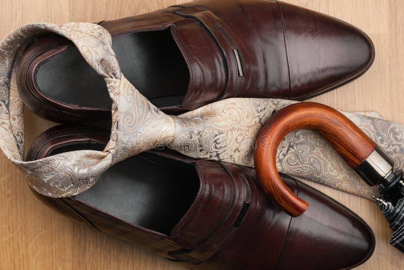 Men& x27; s klassieke toebehoren: bruine schoenen, band, paraplu op een houten oppervlakte stock afbeelding