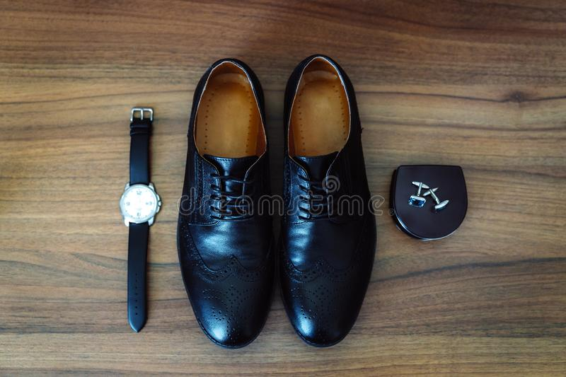 Men`s leather shoes, watches and cufflinks on the background of a brown table. Clothing accessories businessman. Concept. Of grooms accessories at wedding day stock photo