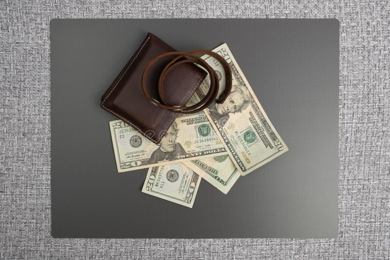 Men`s leather wallet with dollar bills. Leather bracelet casual. Dollar bills on gray background. Men`s leather wallet with dollar bills. Leather bracelet stock photography