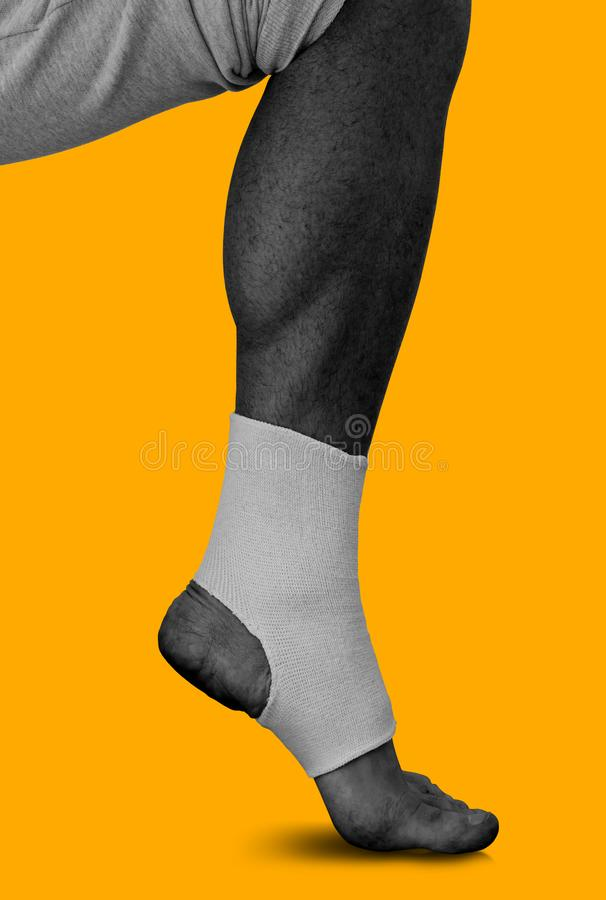 Men`s leg in an elastic bandage on ankle  on yellow stock photography