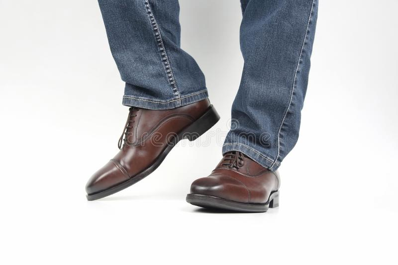 Men`s legs in jeans shod in classic brown Oxford shoes. The Men`s legs in jeans shod in classic brown Oxford shoes stock photography