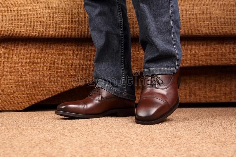 Men`s legs in jeans shod in classic brown Oxford shoes. The Men`s legs in jeans shod in classic brown Oxford shoes stock images
