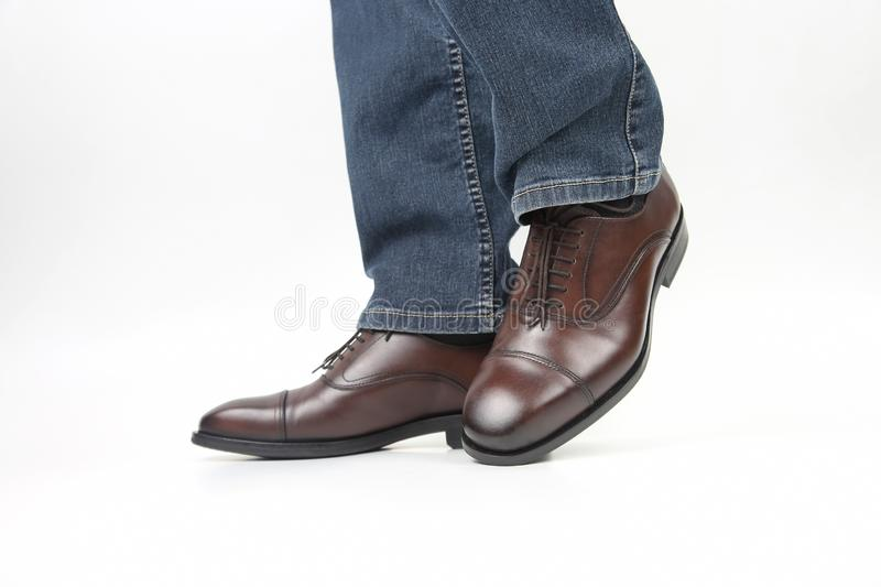 Men`s legs in jeans shod in classic brown Oxford shoes. The Men`s legs in jeans shod in classic brown Oxford shoes royalty free stock image