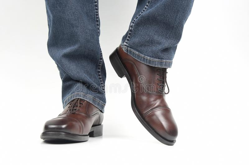 Men`s legs in jeans shod in classic brown Oxford shoes stock photo