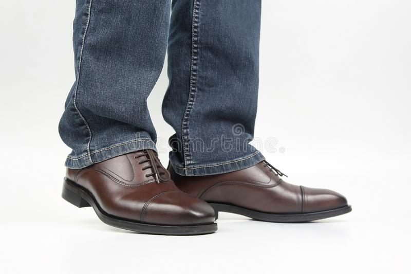Men`s legs in jeans shod in classic brown Oxford shoes. The Men`s legs in jeans shod in classic brown Oxford shoes stock image